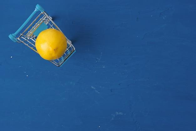 Zitrone im einkaufswagen auf klassischem blauen tisch, draufsicht