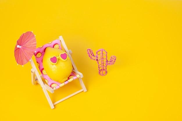 Zitrone in der sonnenbrille im sonnenbett mit regenschirm