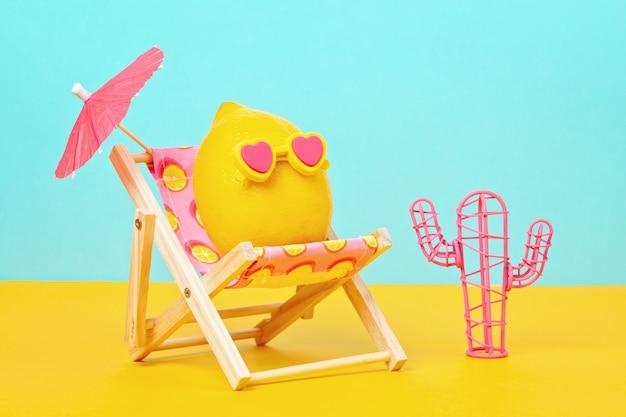 Zitrone in der sonnenbrille im sunbed mit umbrela am strand