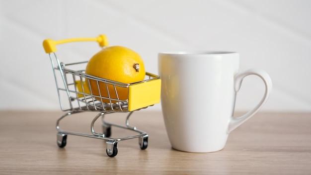 Zitrone in einem kleinen einkaufswagen auf dem küchentisch. in der nähe steht eine weiße tasse tee. heller und moderner küchenhintergrund.