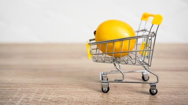 Zitrone in einem supermarktwagen auf küchentisch - hölzerner hintergrund. online-shopping-konzept. konzept mit kleinem budget