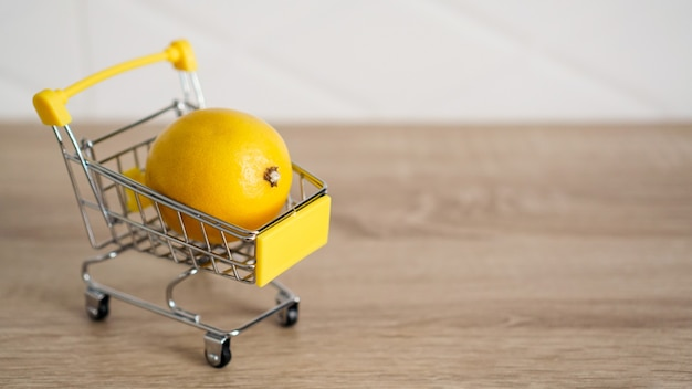 Zitrone in einem supermarktwagen auf küchentisch - hölzerner hintergrund. online-shopping-konzept. konzept mit kleinem budget Premium Fotos