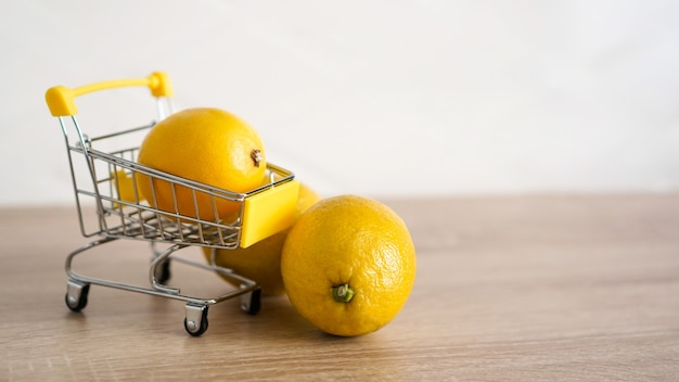 Zitrone in einem supermarktwagen auf küchentischhintergrund. zwei zitronen neben dem wagen. online-shopping-konzept.