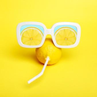 Zitrone in sonnenbrille auf gelb. sommer saftige farbe.