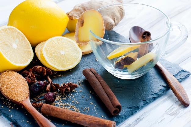 Zitrone, ingwer, zucker und gewürze - zutaten für einen würzigen wärmenden tee