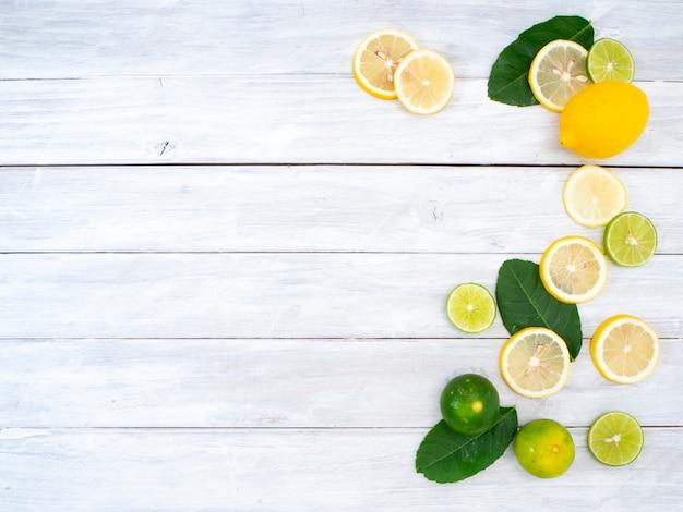 Zitrone mit blättern auf weißem hölzernem hintergrund