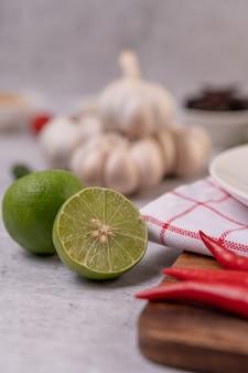 Zitrone mit chili und knoblauch auf einer weißen oberfläche halbieren. selektiver fokus.