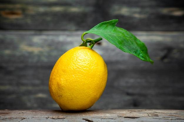 Zitrone mit einer blattseitenansicht auf einem dunklen hölzernen hintergrund