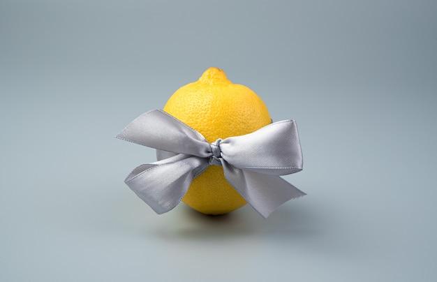 Zitrone mit einer grauen schleife auf einem grauen hintergrund. seitenansicht mit platz zum kopieren.