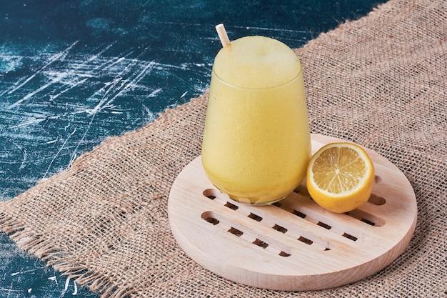 Zitrone mit einer tasse getränk auf blau.