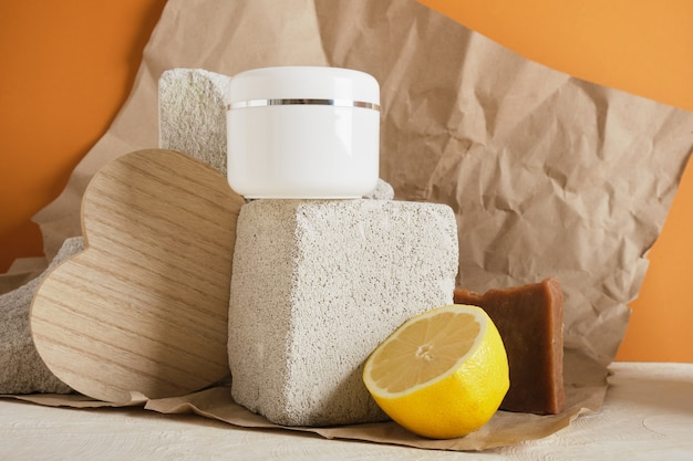Zitrone, natürliche hausgemachte kakaoseife und weißes plastikglas für hautpflegekosmetik auf einem steinpodest auf braunem hintergrund kopieren raum natürliches körperpflegekonzept