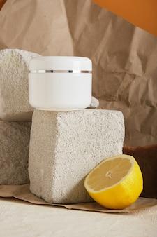 Zitrone, natürliche hausgemachte kakaoseife und weißes plastikglas für hautpflegekosmetik auf einem steinpodest auf braunem hintergrund