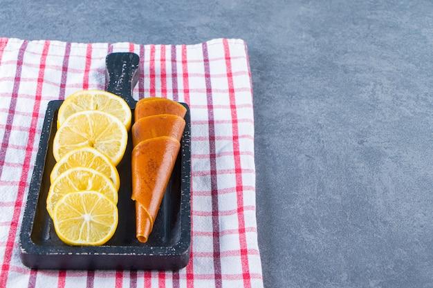 Zitrone säuern und auf einem brett auf dem geschirrtuch auf der marmoroberfläche in scheiben schneiden