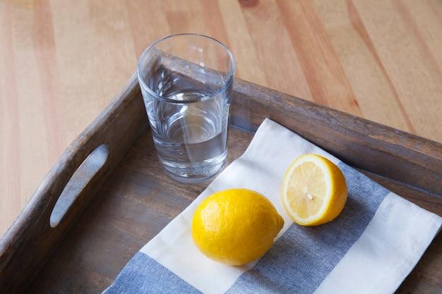 Zitrone, serviette und glas wasser auf einem holztablett.