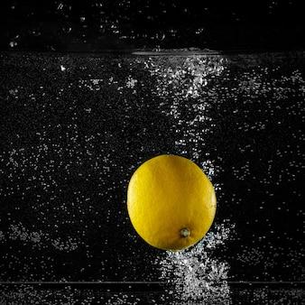 Zitrone spritzt ins wasser auf schwarzem hintergrund