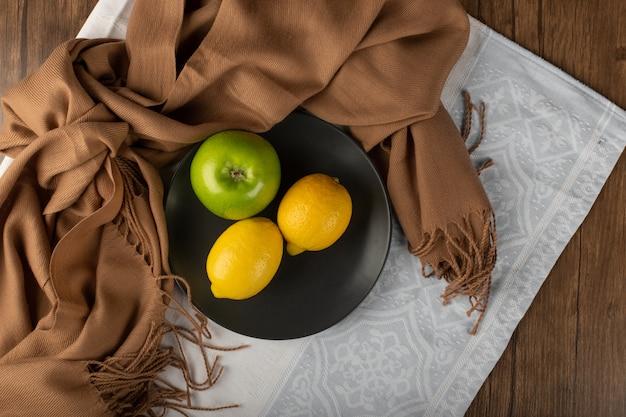 Zitrone und äpfel in einer schwarzen platte. draufsicht
