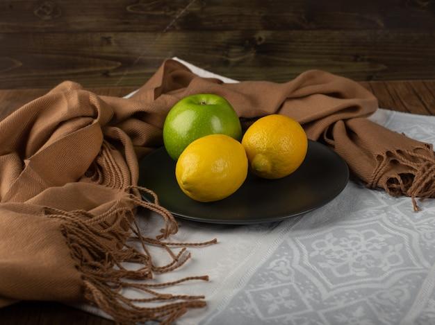 Zitrone und äpfel in einer schwarzen platte.