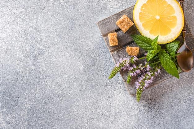 Zitrone und frische minze mit blumen und braunem zucker auf hintergrund