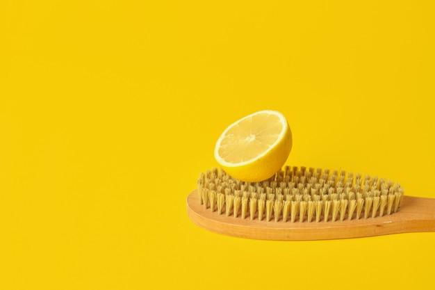 Zitrone und holzbürste auf gelbem hintergrund