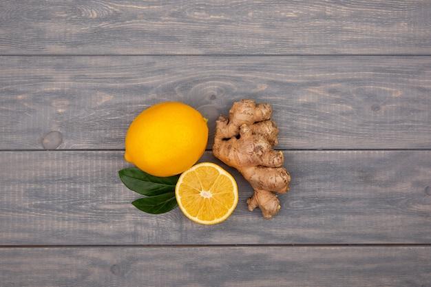 Zitrone und ingwer auf einem hölzernen hintergrund. inhaltsstoffe gegen influenza und viren. zutaten für tee. natürliche medizin.