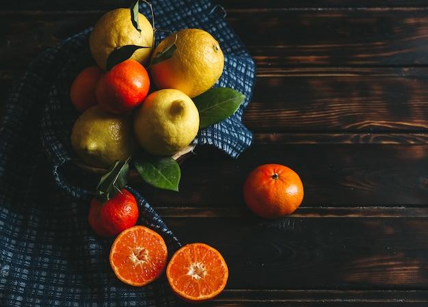 Zitrone und orangenfrüchte in einem korb auf einem rustikalen holztisch