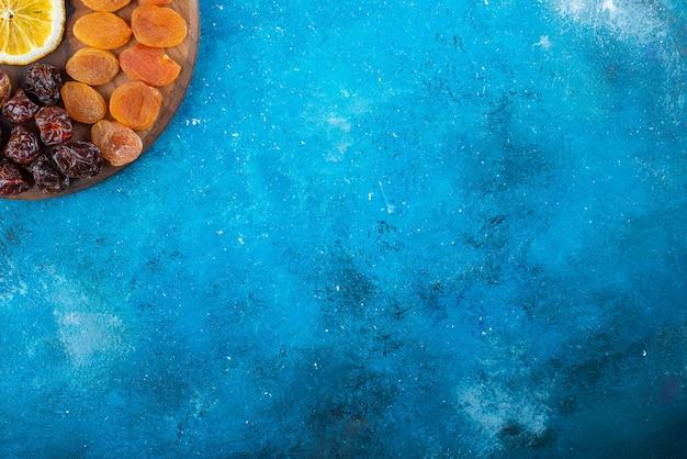 Zitrone und trockenfrüchte auf einem brett auf dem blauen tisch in scheiben schneiden.