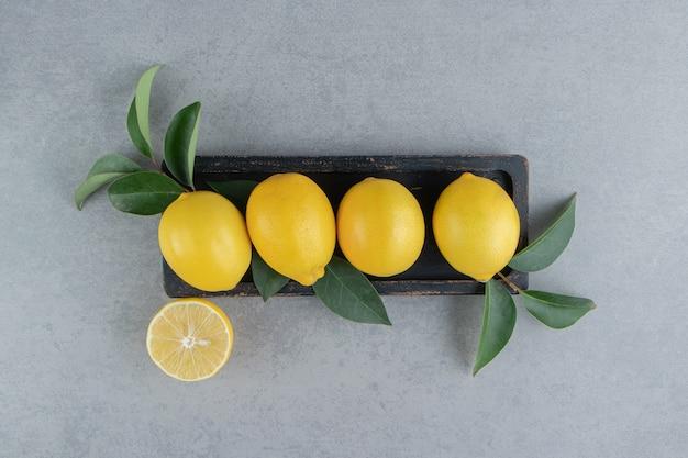 Zitronen auf einem kleinen tablett mit blättern auf marmor geschmückt