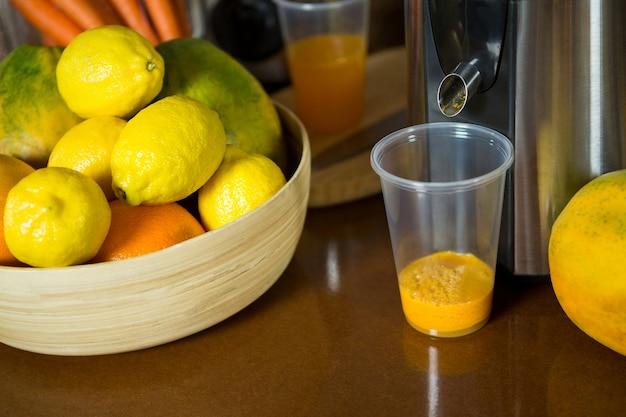 Zitronen auf holzschale mit glas saft an der theke