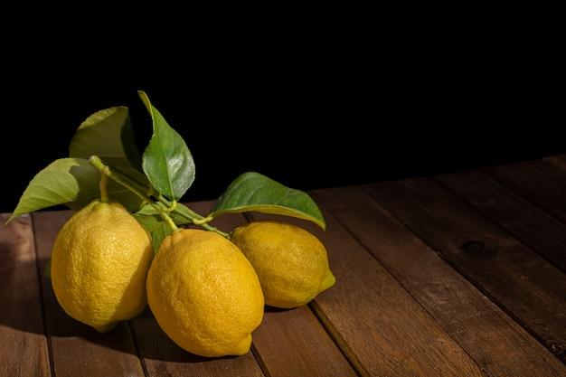 Zitronen auf holztisch mit schwarzem hintergrund