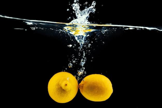 Zitronen, die in das wasser mit einem spritzer gegen schwarzen hintergrund hautnah tauchen