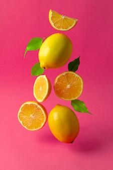 Zitronen, die in der luft gegen helles rosa schweben