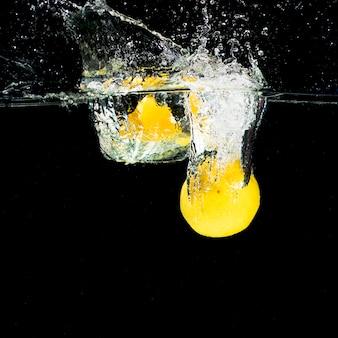 Zitronen, die in wasser fallen, spritzen