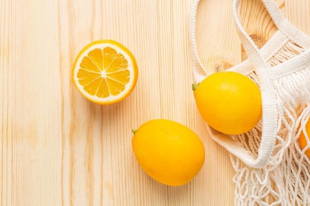 Zitronen in der baumwolleinkaufs-umweltfreundlichen tasche auf hölzernem hintergrund. hilfe bei erkältungen, natürliche heilmittel gegen die krankheit