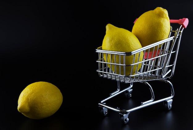 Zitronen in einem wagen auf schwarzem hintergrund