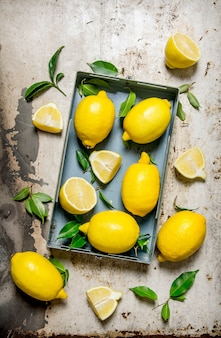 Zitronen in einer metallbox mit blättern. auf rustikalem hintergrund. draufsicht