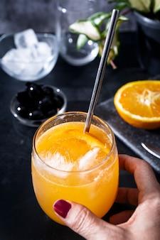 Zitronen-ingwer-kombucha mit einer orangenscheibe trinken