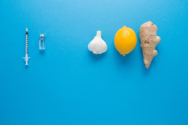 Zitronen-knoblauch-ingwer auf blauem grund. die natürliche abwehr des körpers gegen krankheiten. die wahl, naturheilmittel oder pharmakologie zu nehmen.