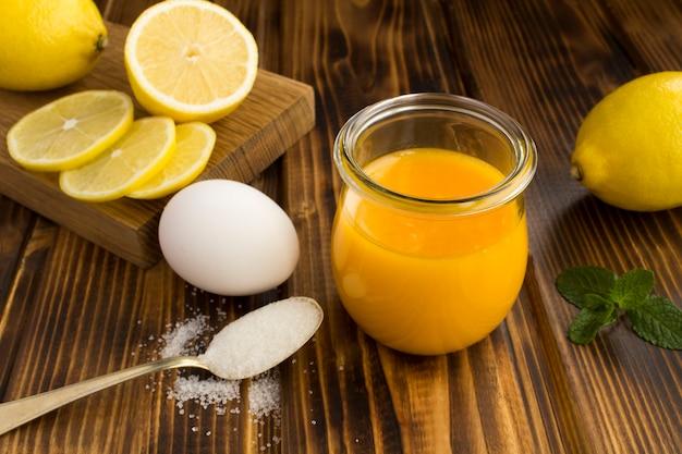 Zitronen-kurd im glas und zutaten auf der braunen holzoberfläche. nahansicht.