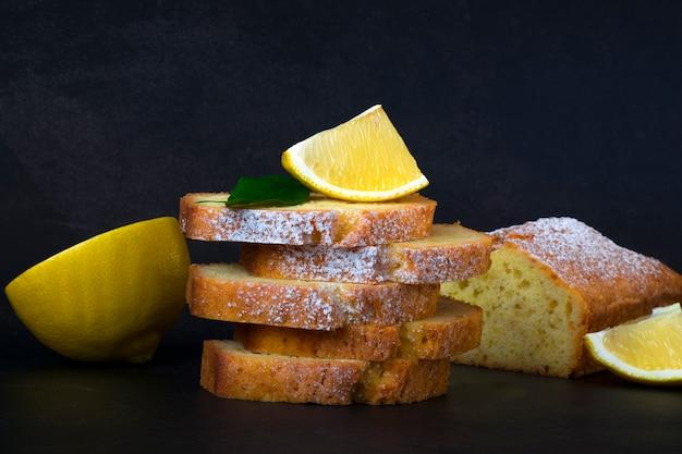 Zitronen-laib-kuchenstücke mit zuckerpulver, zitronenscheibe und pfundkuchen