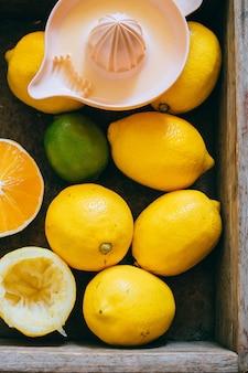Zitronen, limette, orange in einer holzkiste, eine zitruspresse. frische limonade.