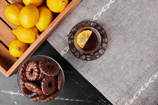 Zitronen lokalisiert auf einem schwarzen hintergrund in einem holztablett mit keksen und einem glas tee herum.