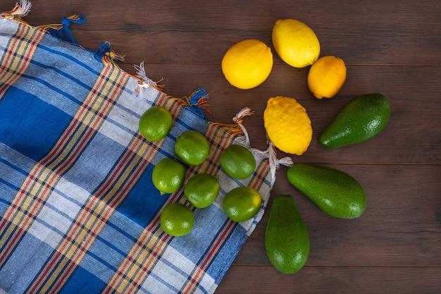 Zitronen mit avocados auf buntem tuch auf braunen holzoberflächenzitrusfrüchten
