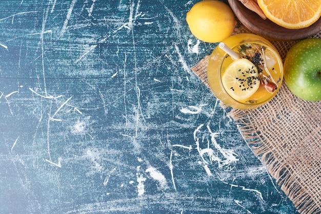 Zitronen mit einer tasse getränk auf blau.