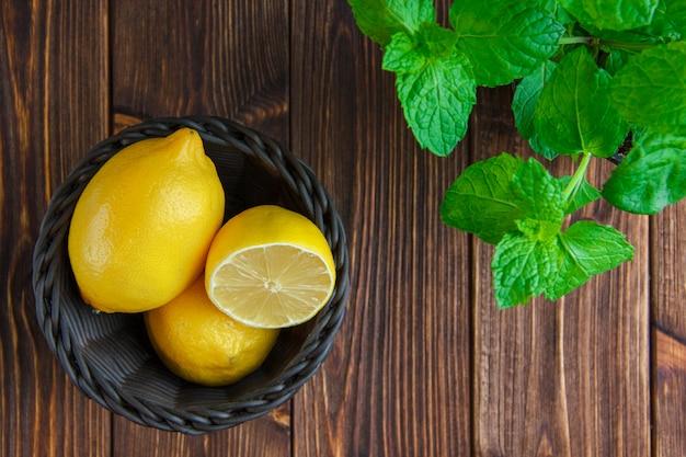 Zitronen mit kräutern in einem weidenkorb auf holztisch, flach liegen.