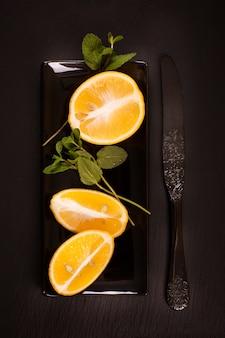 Zitronen mit minze über schwarzen steintisch streichen