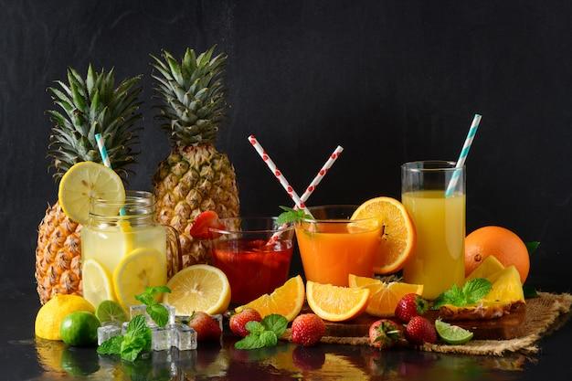 Zitronen-, orangen- und erdbeersaft auf schwarzem