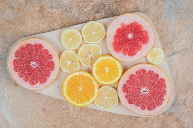 Zitronen-, orangen- und grapefruitscheiben auf holzbrett.