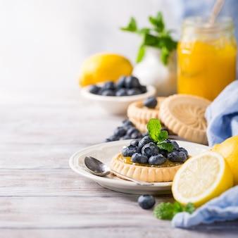 Zitronen-quark-törtchen mit frischen blaubeeren