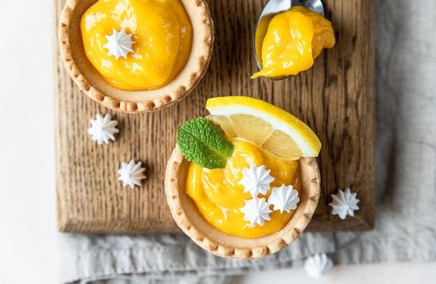 Zitronen-törtchen hausgemachte shortbread-mini-törtchen mit lemon curd und baiser