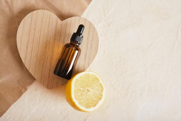 Zitronen- und braunglasflasche mit tropfer für serum oder kosmetisches öl auf einem holzpodest in herzform, umweltfreundliches körperpflegekonzept